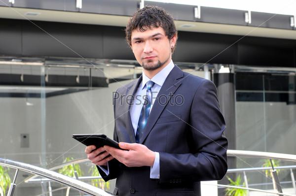 Мужчина с планшетом перед современным зданием