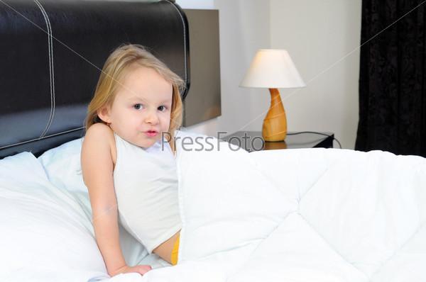Ребенок с одеялом на кровати