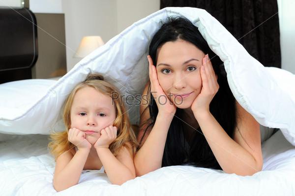 Мать и маленькая девочка вместе под одеялом