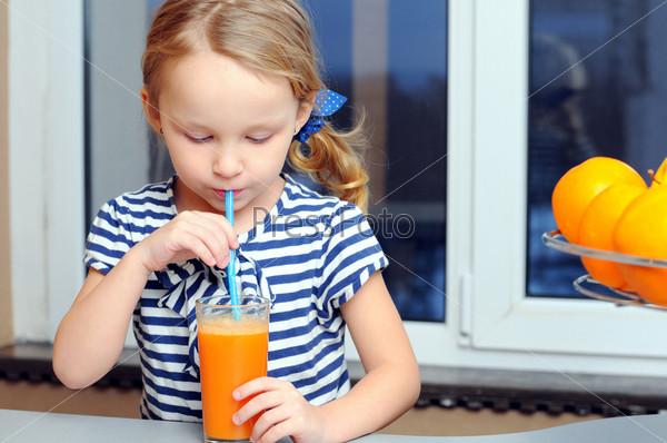 Портрет счастливой маленькой девочки, пьющей апельсиновый сок