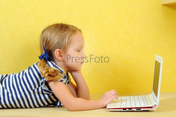 Маленькая девочка лежит на полу с ноутбуком