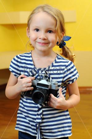 Молодой фотограф держит старый дальномерный фотоаппарат