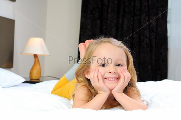 Ребенок на одеяле на кровати