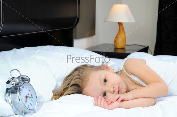 Портрет милой девочки, лежащей в постели
