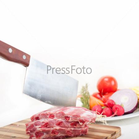 Разделанные свежие свиные ребра и овощи