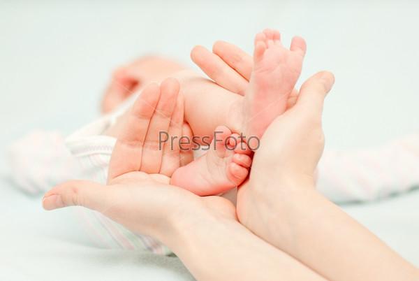 Маленькие детские ноги и руки матери