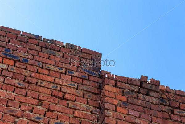 Красная кирпичная стена на фоне голубого неба