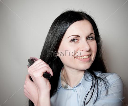 Фотография на тему Улыбающаяся брюнетка расчесывает волосы