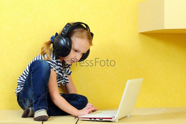 Девочка в наушниках с ноутбуком