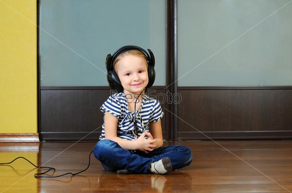 Милая маленькая девочка наслаждается музыкой, используя наушники