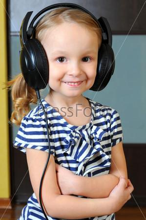 Фотография на тему Милая маленькая девочка наслаждается музыкой, используя наушники