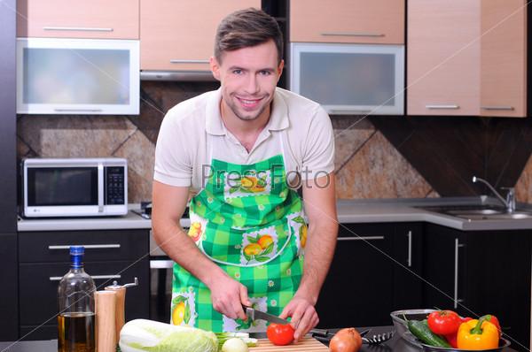 Мужчина в кухне готовит ужин