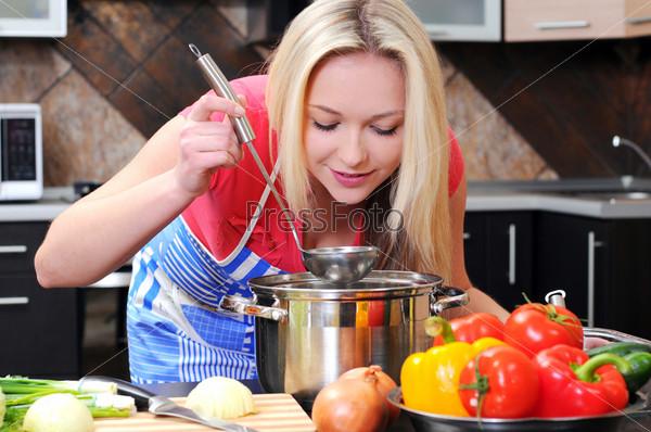 Фотография на тему Счастливая женщина готовит полезный салат в кухне