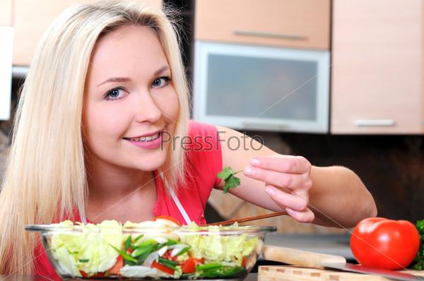 Фотография на тему Улыбающаяся женщина готовит овощи на кухне