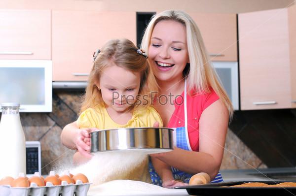 Мать и дочь делают выпечку на кухне