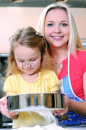 Мать и дочь пекут на кухне
