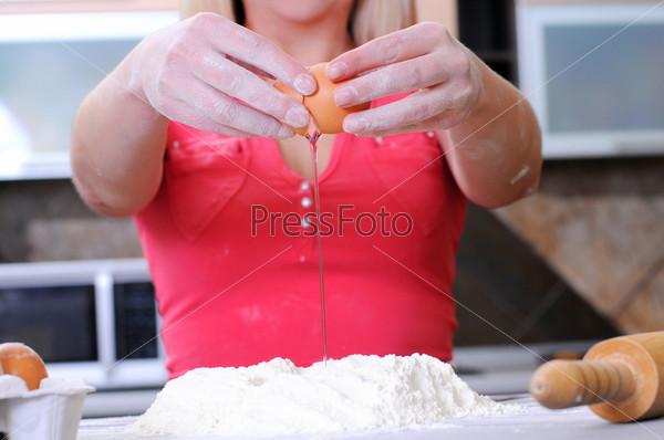 Фотография на тему Молодая женщина месит тесто руками