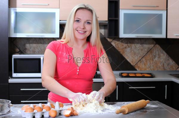 Молодая женщина месит тесто руками