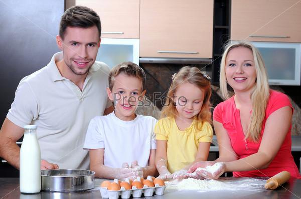 Очаровательная семья вместе печет вкусное печенье на кухне