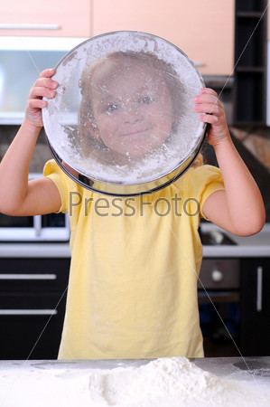 Милая белокурая девочка печет хлеб на кухне