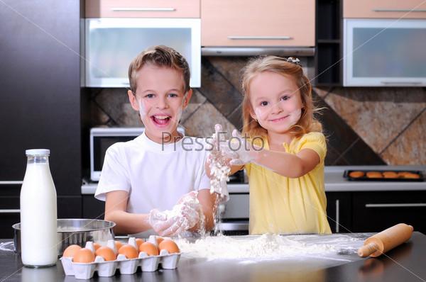 Фотография на тему Дети делают тесто для печенья, пиццы или макарон, весело разбивая яйца