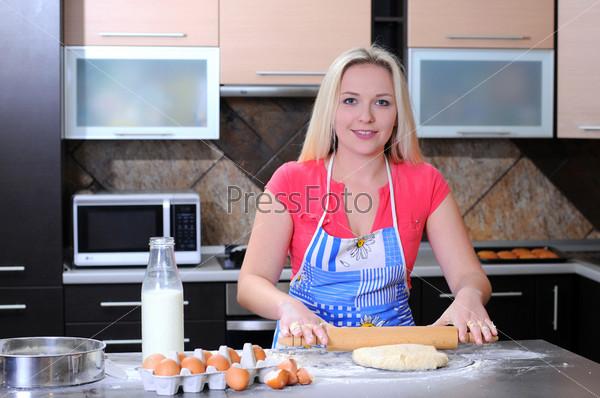 Молодая женщина раскатывает тесто руками