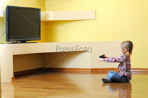 Маленькая девочка играет с консолью