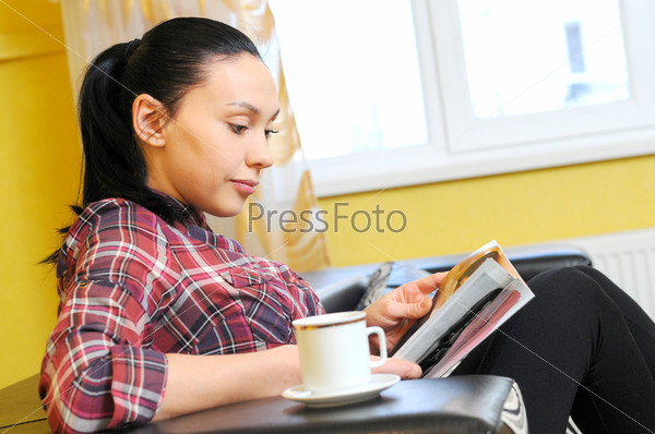 Счастливая расслабленная молодая женщина с чашкой кофе на диване