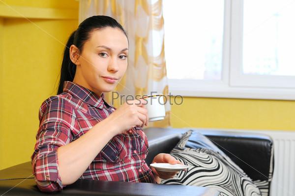 Фотография на тему Счастливая расслабленная молодая женщина с чашкой кофе на диване