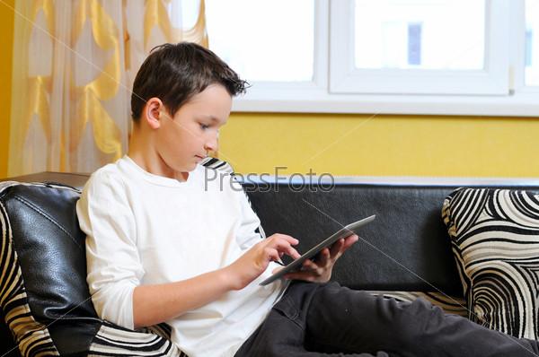 Фотография на тему Маленький мальчик сидит в диване с планшетом