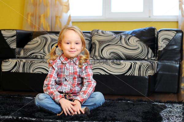 Счастливая маленькая девочка лежит на полу