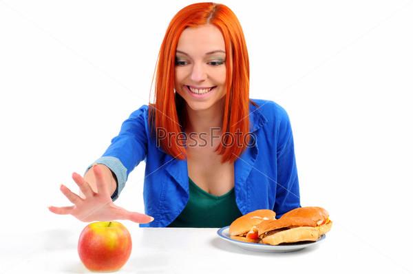 Фотография на тему Хорошенькая молодая девушка решает что поесть: яблоко или гамбургер