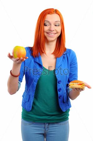 Хорошенькая девушка делает выбор между яблоком и гамбургером