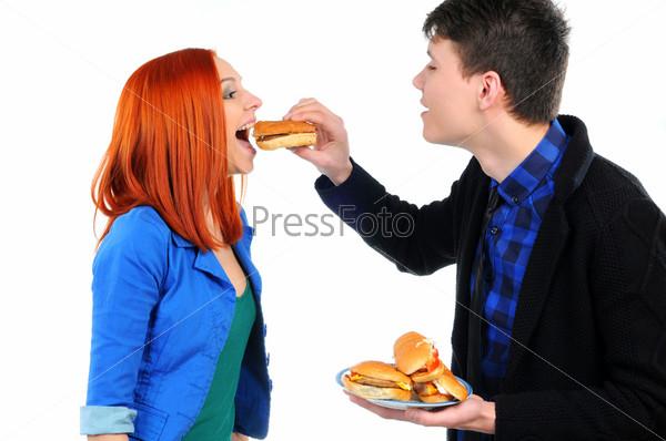Фотография на тему Молодые люди едят гамбургер