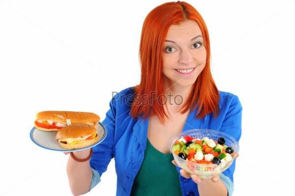 Хорошенькая молодая женщина делает выбор между салатом или быстрым питанием, изолированная на белом фоне