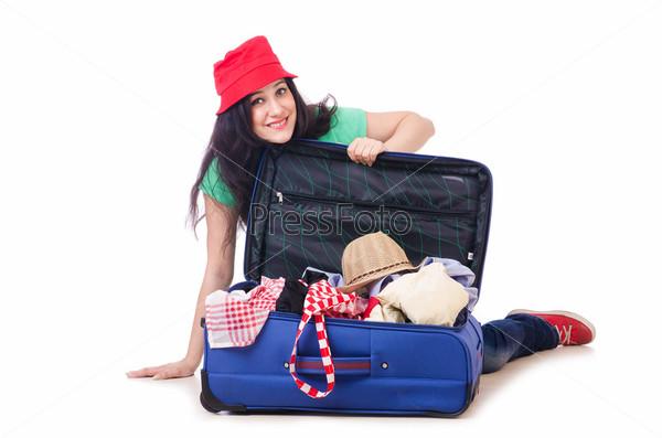 Молодая девушка складывает вещи для поездки