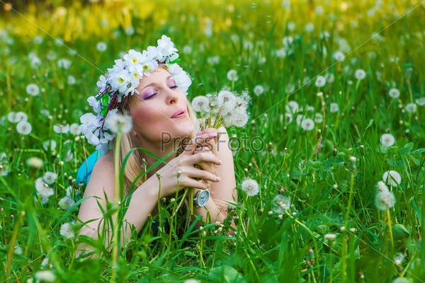 Молодая женщина дует на одуванчик на поле