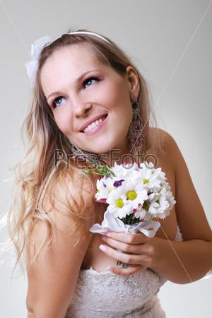 Красивая молодая женщина в белом платье с букетом цветов
