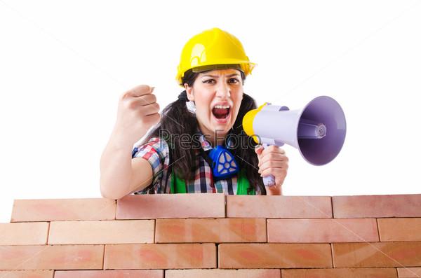 Женщина с мегафоном у кирпичной стены