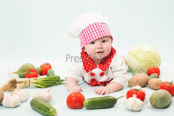 Фотография на тему Девочка в колпаке повара с овощами. Концепция здорового питания