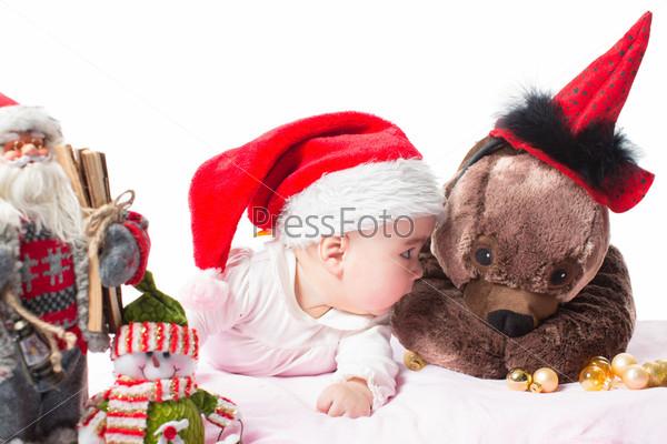 Девочка в новогоднем колпаке с игрушкой, изолированная на белом фоне. Понятие детства и праздника