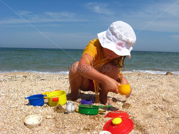 Маленькая девочка играет на море