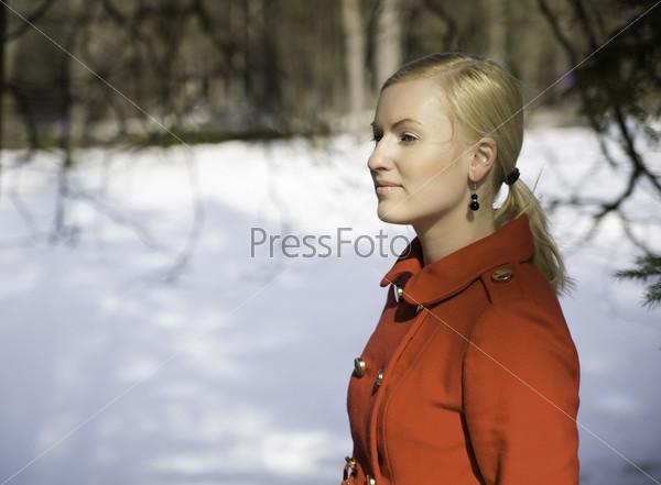 Молодая женщина в пальто думает о чем-то