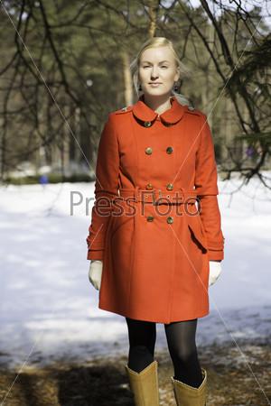 Молодая женщина в красном пальто под елью