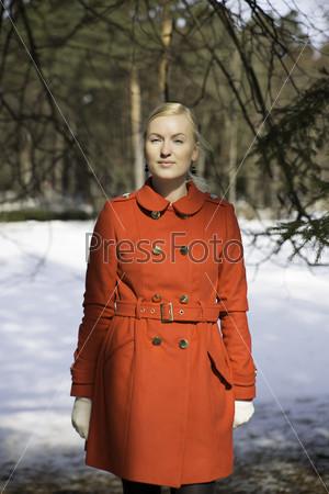 Молодая женщина в пальто позирует под елью