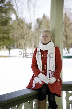 Женщина в красном пальто мечтает, сидя на перилах