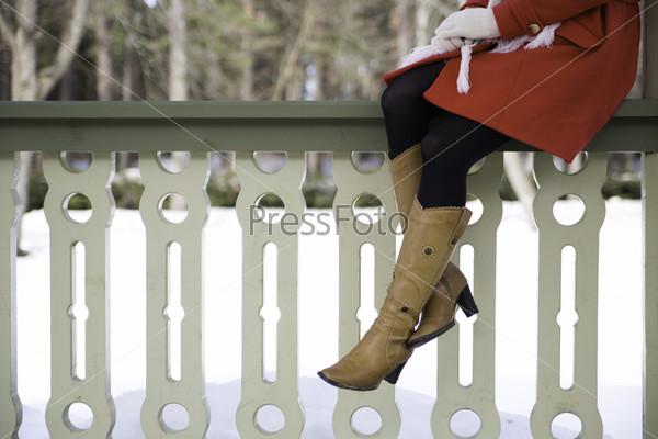 Женские ноги в сапогах на перилах террасы