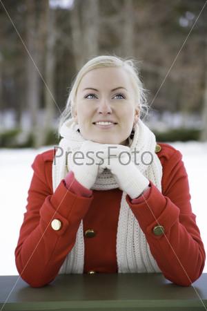 Женщина мечтает, опираясь на перила террасы