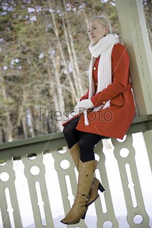 Женщина сидит на перилах террасы