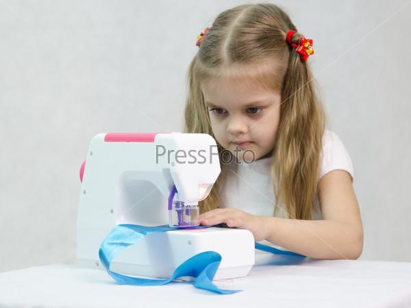 Девочка шьет на швейной машинке